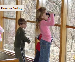Children looking out window with binoculars at Powder Valley Nature Reserve