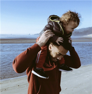 Dad carrying child on his shoulders.