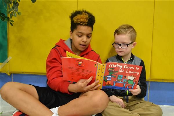 "NKMS Student Jaden Walker reads ""Maisy Goes to the Library"" to Oak Hill student Aiden Hundele."